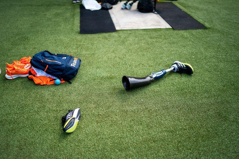 Een prothese ligt op het veld tijdens de training van het Nederlandse atletiekteam. Beeld Inge Hondebrink