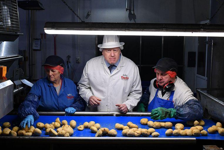 Johnson zet een bedenkelijke blik op terwijl hij zich verdiept in de kwaliteit van aardappelen tijdens een bezoek aan de Tayto Castle-chipsfabriek in Noord-Ierland.