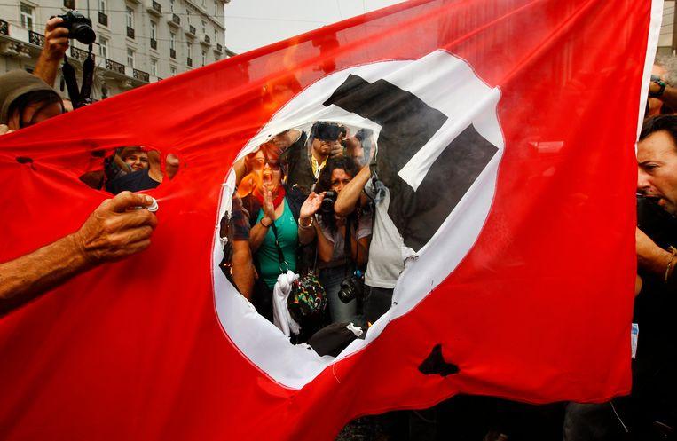 Een Nazivlag wordt verbrand tijdens een bezoek van Merkel aan Athene. Beeld null