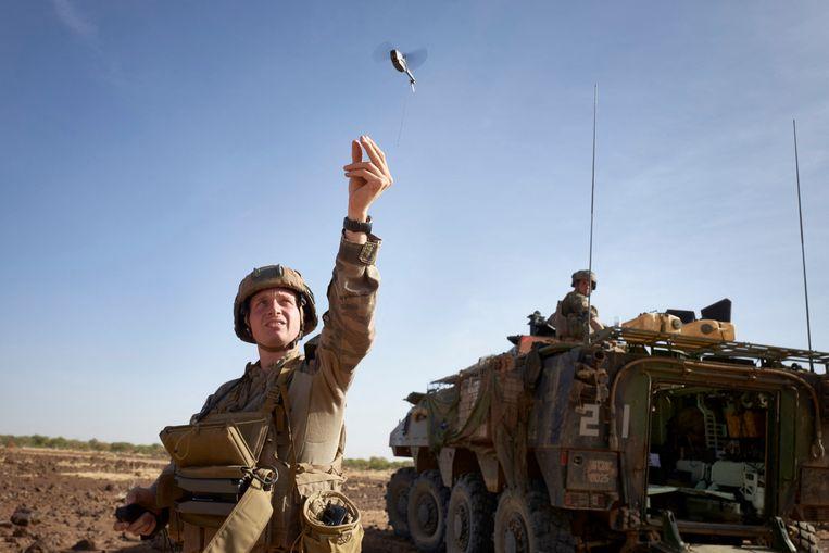 Een Franse militair in Burkina Faso lanceert een mini-drone om te controleren of er zich in de buurt jihadisten schuilhouden.  Beeld Hollandse Hoogte / AFP