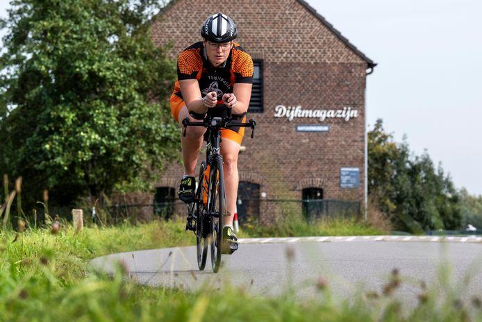 Marloes Vos traint op de dijk in Bemmel voor haar tweede triatlon.