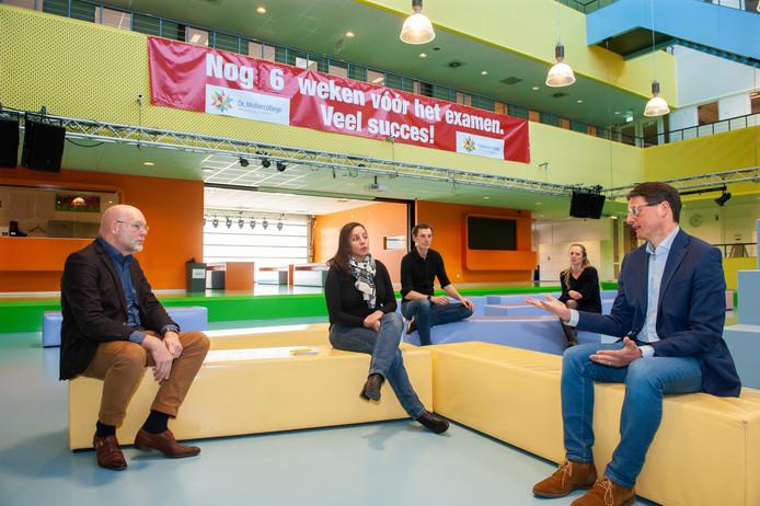 Achteraf slaat het spandoek in de aula van het Dr. Mollercollege in Waalwijk als een tang op een varken. Dankzij corona dus. Directeur Kees Maas (links) bespreekt met enkele medewerkers wat hen nu te doen staat.