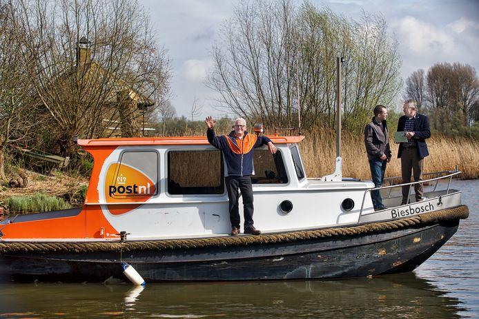 Schrijver Kees Schuller (geheel rechts) reikt het eerste exemplaar van een boek over postbezorging in de Biesbosch uit aan Jan Saarloos, die met zijn vader het laatste boerenbedrijf in de Biesboch runt. Voormalig postbode Cor de Wijs zwaait er vrolijk bij op de boot, waar hij een dag in de week de post mee bezorgt.