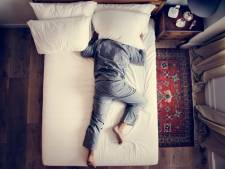 In het gesloten, felverlichte fastfoodrestaurant lag een man op een bankje te slapen