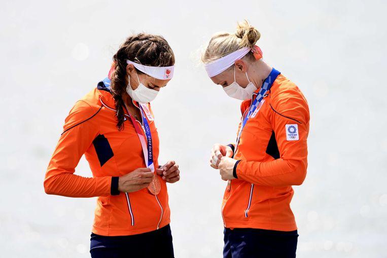 Lisa Scheenaard (r) en Roos de Jong aanschouwen hun bronzen medaille. Beeld ANP