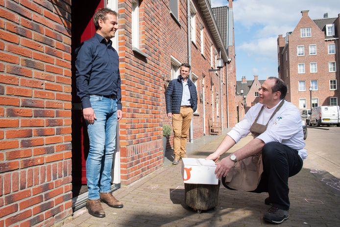 Kok Marcel Verdaasdonk van Koken aan de Markt bezorgt, op gepaste afstand, de eerste Heldfood aan initiatiefnemer Rob van Dongen (L). Op de achtergrond makelaar Marco Verbrugge.
