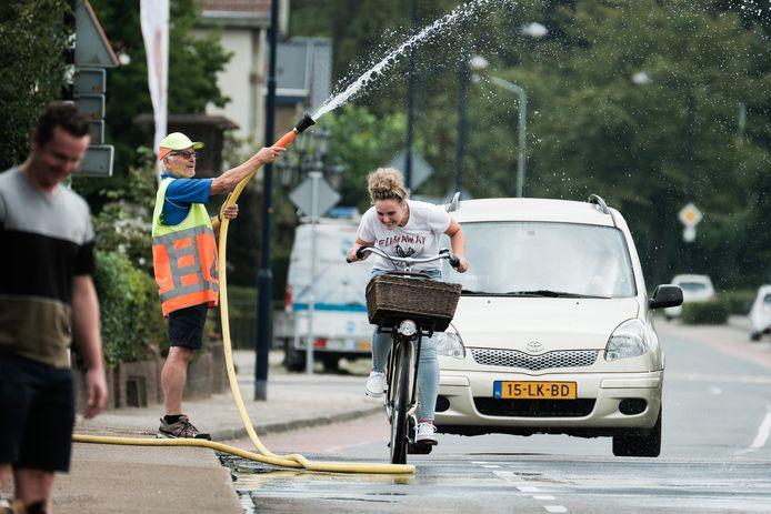 Henk Damen, die het hete asfalt in Terborg koelt met water uit een slang, heeft daarbij een extraatje bedacht voor verhitte fietsers: hij tilt de slang op zodat de fietser wat verkoeling krijgt om de hete 30 graden te bestrijden.