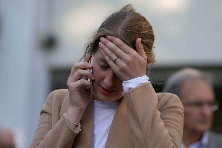 Een vrouw aan de telefoon: ze kan nog niet goed geloven wat er is gebeurd. Beeld afp