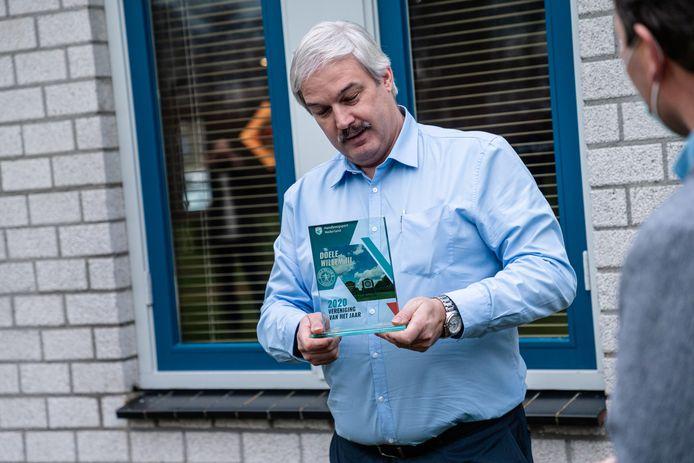 Voorzitter Freddy van den Hoogen van Doele Willem III uit Boekel ontvangt de trofee voor handboogvereniging van het jaar uit handen van bondsdirecteur Arnoud Strijbis.