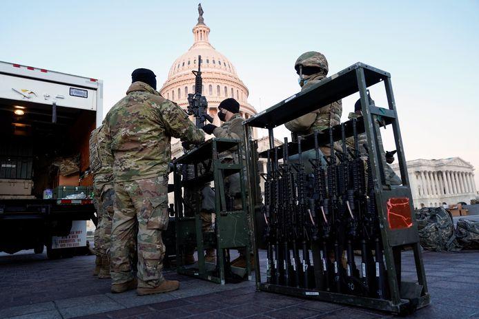 Leden van de Nationale Garde krijgen wapens aan de ingang van het Capitool.