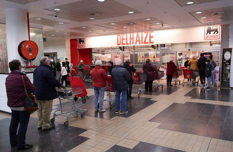Een rij voor de Delhaize in Brussel onder coronatijd.  Beeld REUTERS