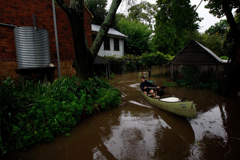 Elliot Sullivan, de 15-jarige zoon van Ben Sullivan, vaart met een kano door hun ondergelopen tuin in Windsor. Beeld Dean Sewell / Oculi Photos