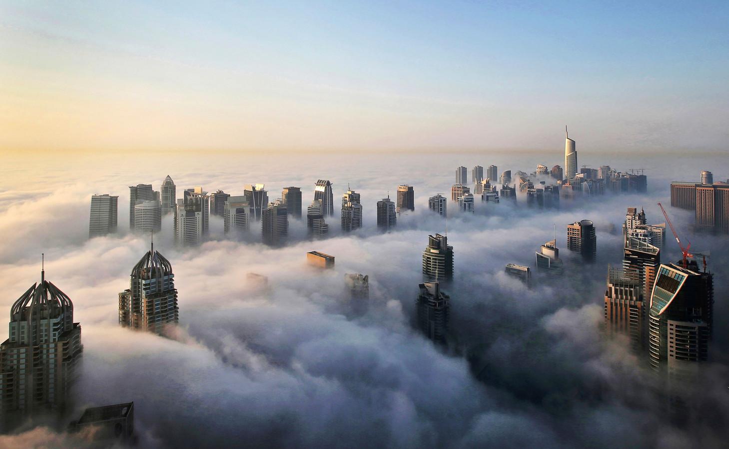 Toppen van wolkenkrabbers boven de wolken in Dubai.