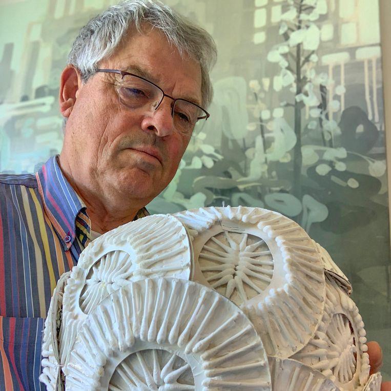 Jos van den Broek met een model van Emiliania huxleyi, een alg die algemeen voorkomt in de zeeën en oceanen. Zelf gemaakt, van papieren bordjes en wattenstaafjes. Beeld Jos van den Broek