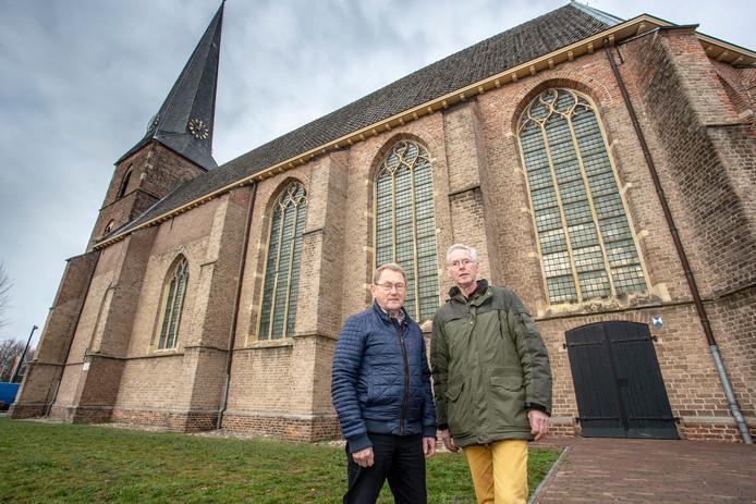 Henk Droppers en Gerrit Vlogman voor de nog te restaureren glad-in-loodramen van de Dorpskerk in Vorden. Het tweetal riep de Vordense gemeenschap bijeen om bij te springen om de restauratie te bewerkstelligen.