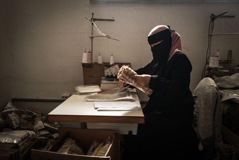 Oeigoerse vrouw aan het werk in een kleine textielfabriek in het district Selimpasa. Beeld Nicola Zolin