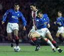 Luc Nilis in duel met Giovanni van Bronkchorst en Derek McInness op 20 oktober 1999 op Ibrox.