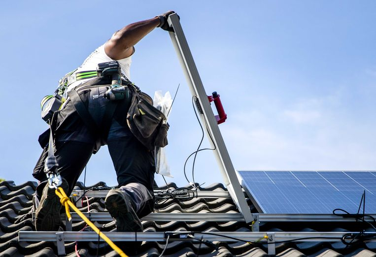 Een installateur plaatst zonnepanelen op het dak van een woonhuis in Gouda. Beeld ANP