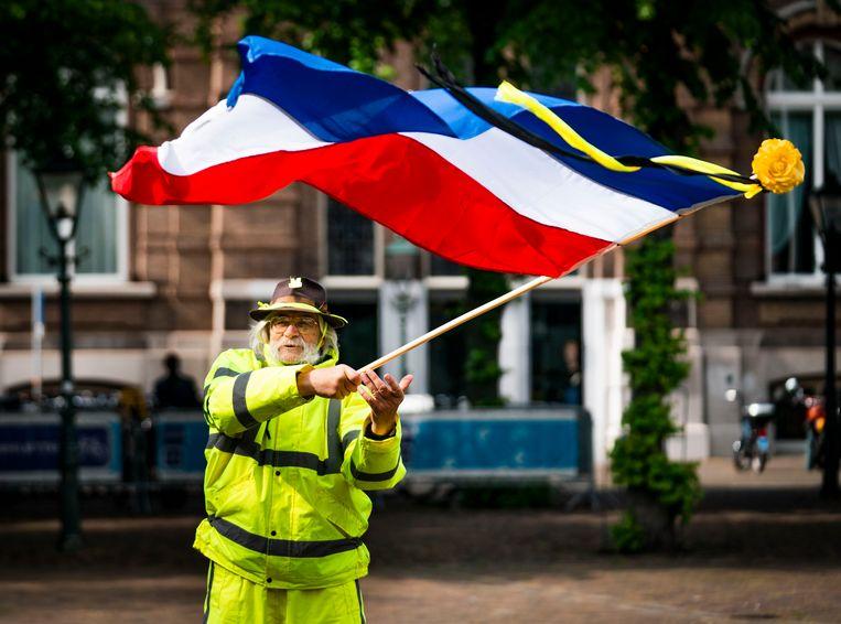 De aanhangers van de gele hesjes zwaaien met ondersteboven hangende Nederlandse vlaggen. Geen rood-wit-blauw, maar 'Blauw-wit-rood, Nederland in nood!'.  Beeld Freek van den Bergh / de Volkskrant