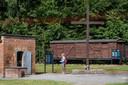 Een bezoeker van het museum staat naast de gaskamer van het voormalige concentratiekamp