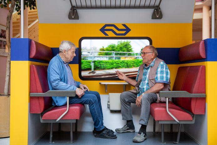 De broers Toon (rechts) en Engel Blansert in de door NS en Alzheimer Nederland nagebouwde treincoupé, die deze maand in het Reinalda Huis in Haarlem staat.