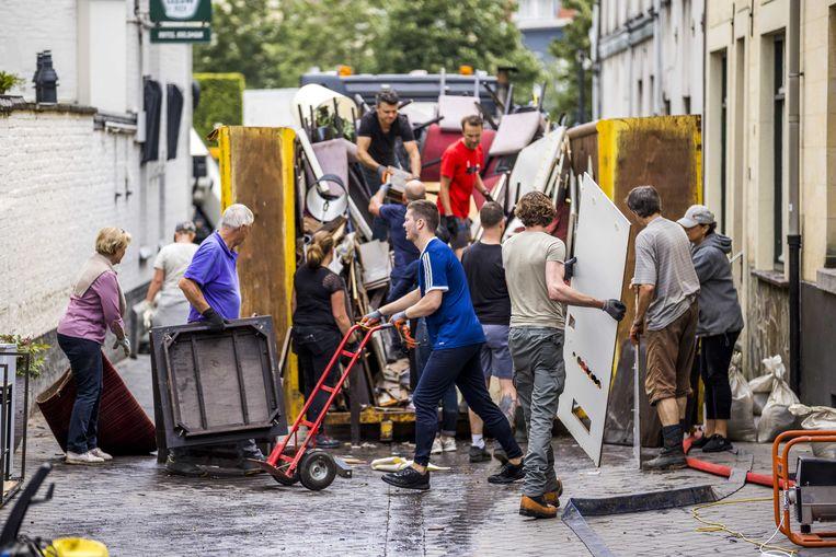 Inwoners ruimen puin na de wateroverlast in Valkenburg aan de Geul. Beeld ANP