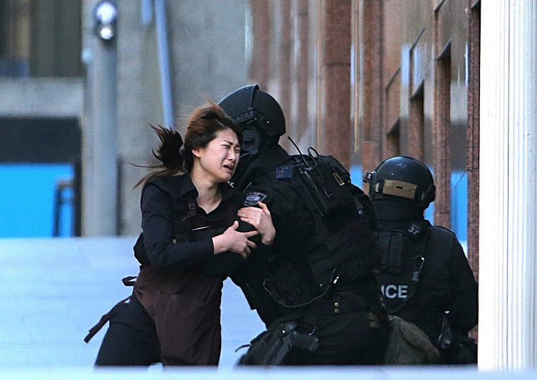 Een gijzelaar is kunnen ontsnappen aan de gijzelnemer en wordt opgevangen door een Australische politieagent. Beeld ap