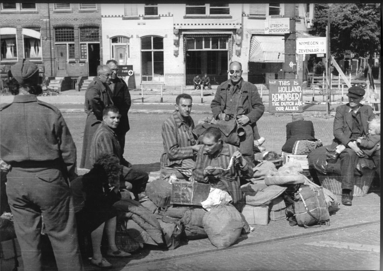 Overlevenden uit concentratiekamp Buchenwald wachten op een lift naar huis op de hoek van de Zijpendaalseweg en Sweerts de Landasstraat in Arnhem in juni 1945.