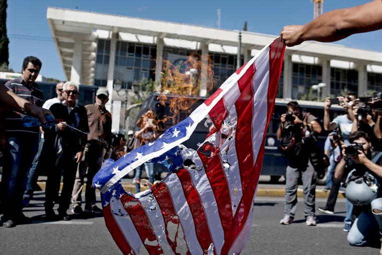 Een Amerikaanse vlag wordt aan flarden gescheurd in Athene. Beeld EPA