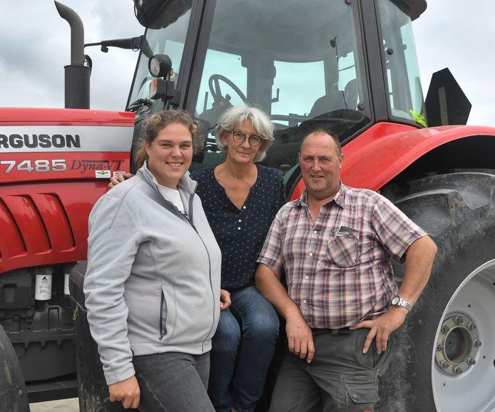 Dominique Cammaert (links) met haar ouders Jorien en Rudi Cammaert bij de grootste tractor van de boerderij.