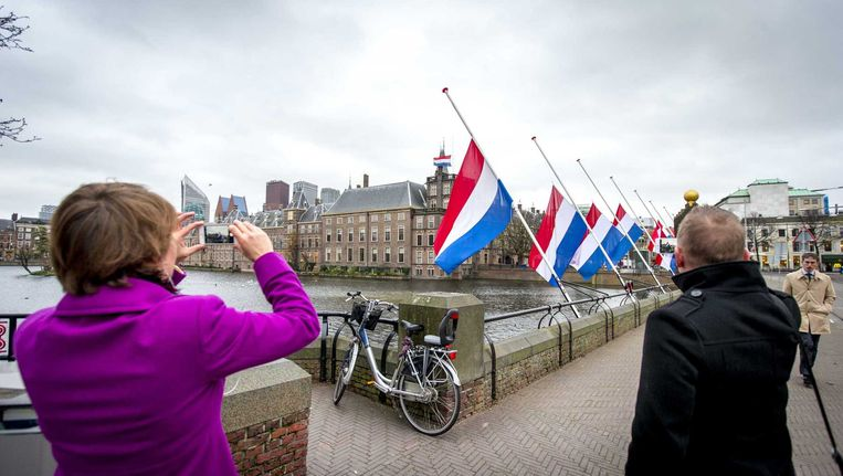 Bij de Hofvijver in Den Haag hangen de vlaggen halfstok in verband met de aanslagen in Parijs. Beeld anp