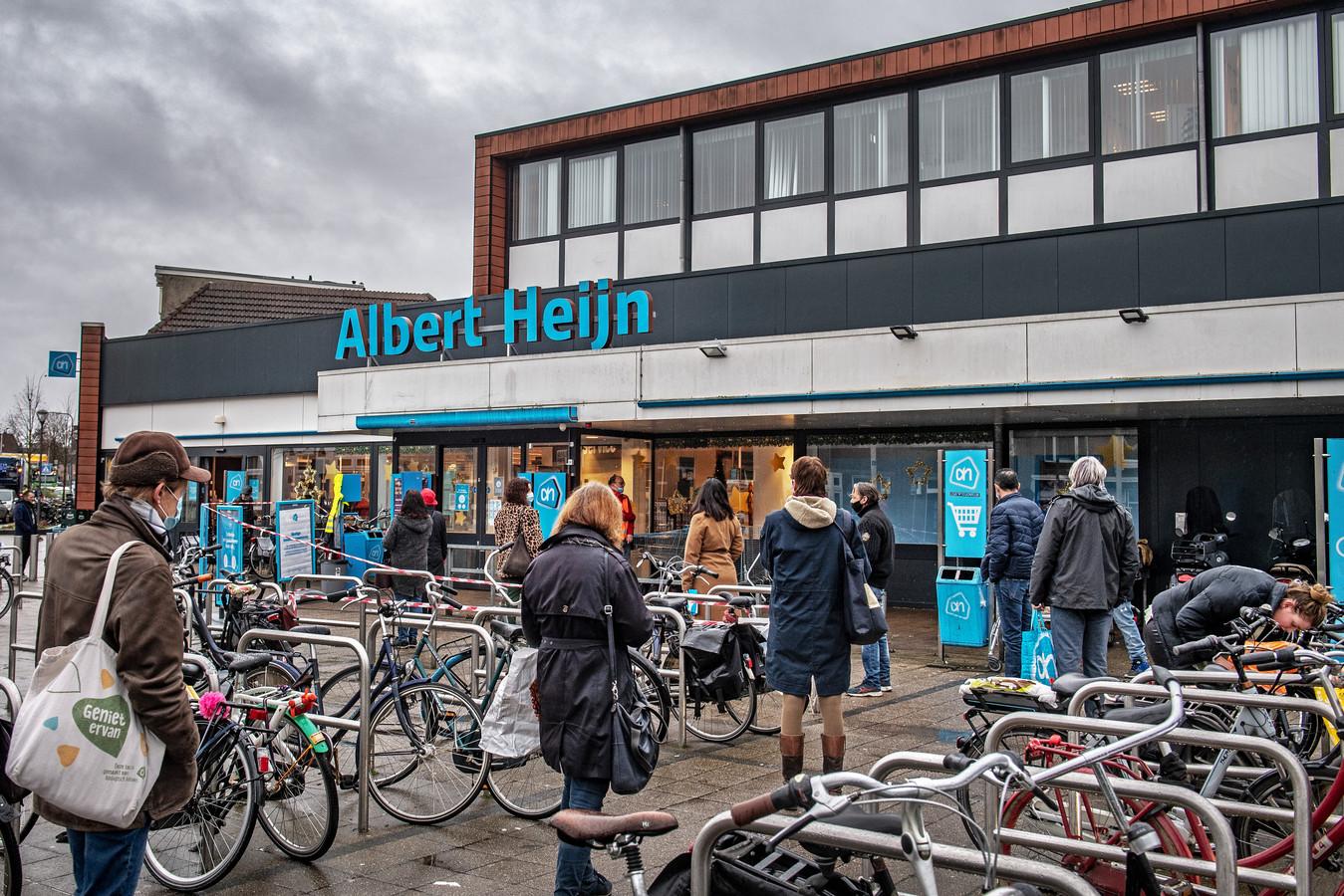 Een lange rij wachtenden woensdagmiddag voor Albert Heijn aan de Daalseweg in Nijmegen. Alle beschikbare winkelwagentjes  zijn in gebruik.