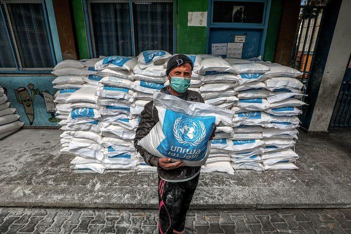 Een man poseert met VN-voedselpakketten in Gazastad.