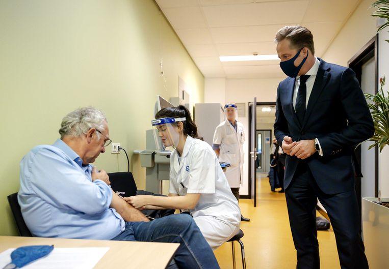 Een medewerker dient een vaccin tegen tuberculose toe dat zou kunnen helpen tegen de gevolgen van corona, tijdens een bezoek van minister Hugo de Jonge. Beeld ANP