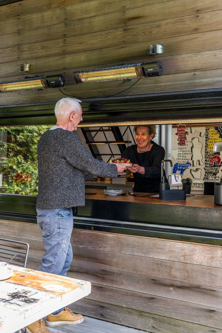 Via het raam boven het aanrecht geven Albert en Greet gemakkelijk eten en drank door naar het terras. 'Dit noemen we onze bar.' Beeld Luc Roymans