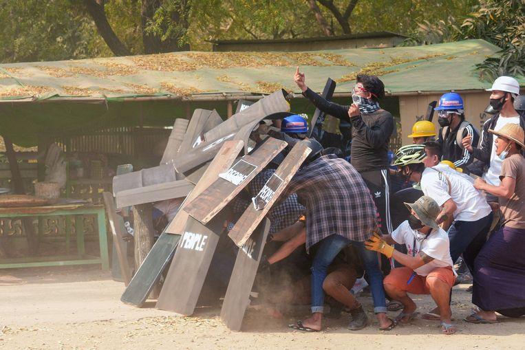 Een demonstrant gebaart naar ordetroepen terwijl hij met anderen dekking zoekt tijdens protesten in de stad Nyaung U. Beeld AFP