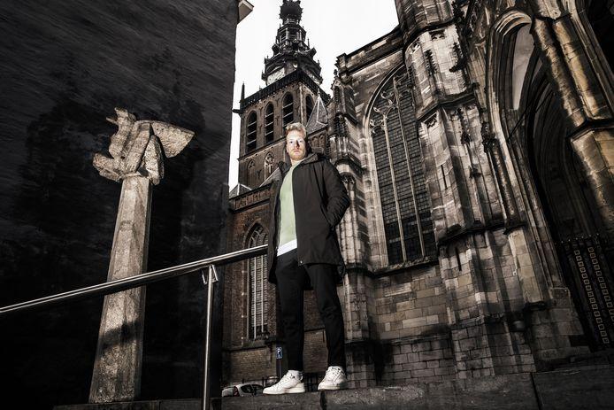 Youri Loen in Nijmegen bij het beeld van de duivel Moenen met de Sint Stevenskerk op de achtergrond.
