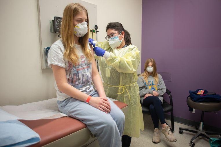 De Amerikaanse Isabelle King (14) krijgt een dosis van het Moderna-vaccin in Houston. Haar tweelingzus Alexandra kijkt toe. Beeld HH / The New York Times Syndication