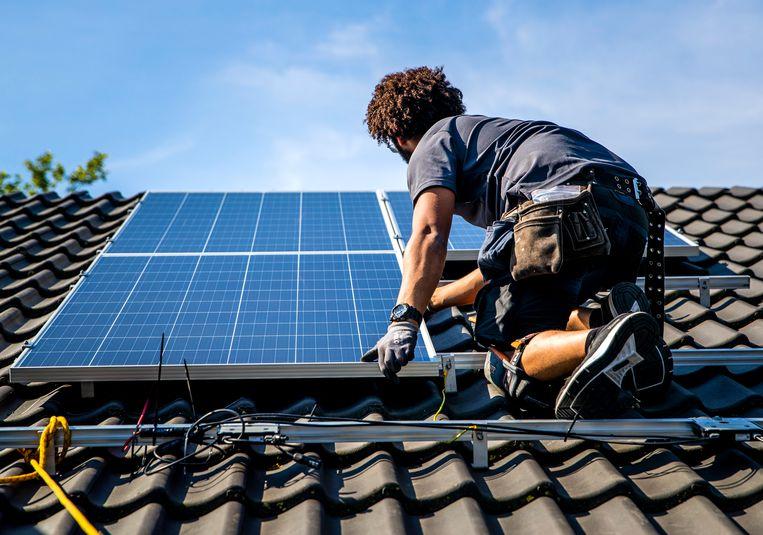 Een installateur plaatst zonnepanelen op het dak van een woonhuis. Beeld Hollandse Hoogte /  ANP