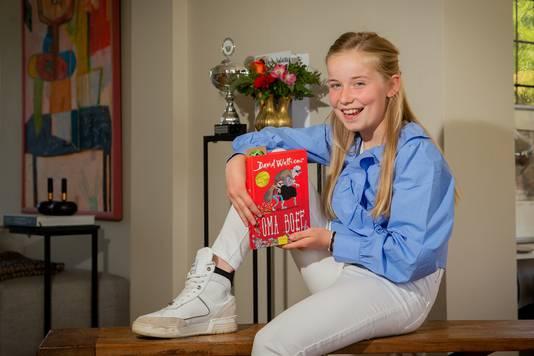 """Juliëtte Liebregts doet woensdag mee aan finale van de Landelijke Voorleeswedstrijd. Achter haar prijkt de trofee die ze won door de Gelderse finale te winnen. ,,Je doet mee omdat het leuk is, maar ook om te winnen."""""""