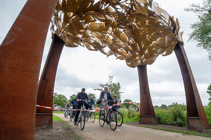 Kunstenaar Peter Pel (met hoed) en wethouder Patrick van der Velden (midden) fietsen onder de Bospoort door en nemen zo het kunstwerk oficieel in gebruik.