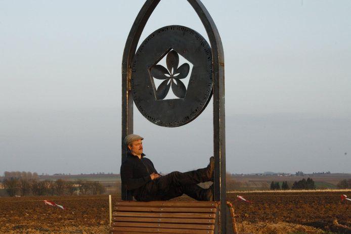 Beeldhouwer Wilfried de Cock met zijn kunstwerk 'mimesis' in betere tijden, toen vandalen het werk nog niet hadden beschadigd.