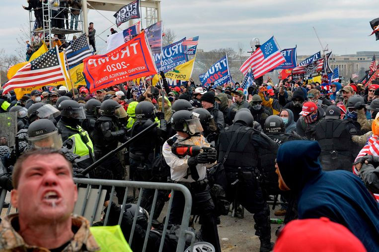Politie en veiligheidstroepen proberen Trump-supporters terug te dringen.  Beeld AFP
