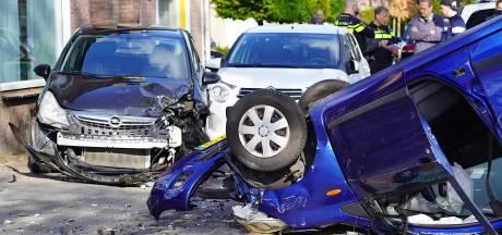 Auto ramt andere geparkeerde auto's en vliegt over de kop in Dongen