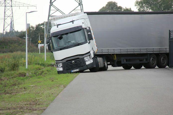 De vrachtwagen zakte weg in de zachte berm.