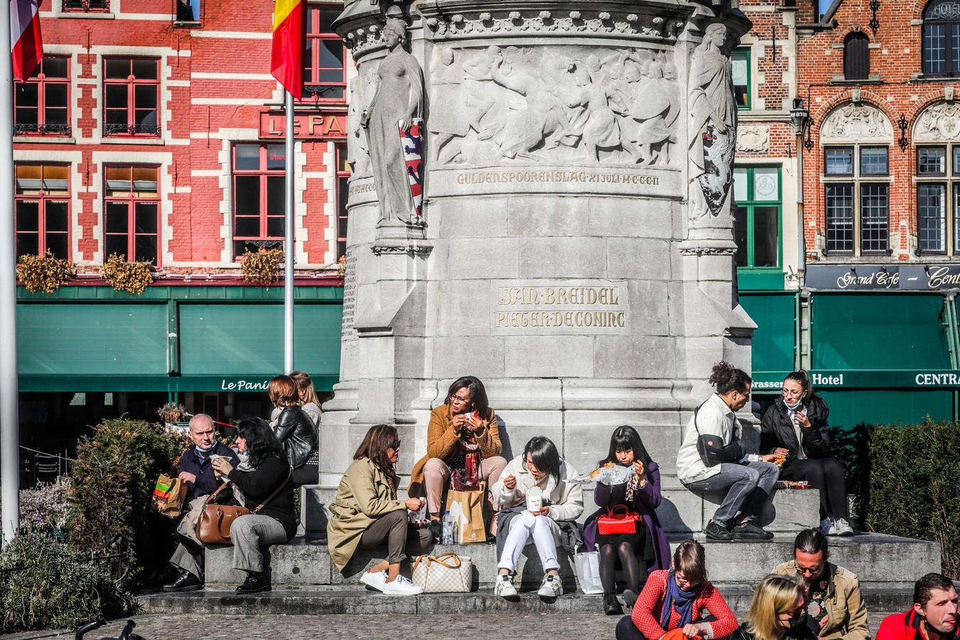 Etende mensen op de Markt in Brugge, terwijl de restaurants erachter gesloten zijn.