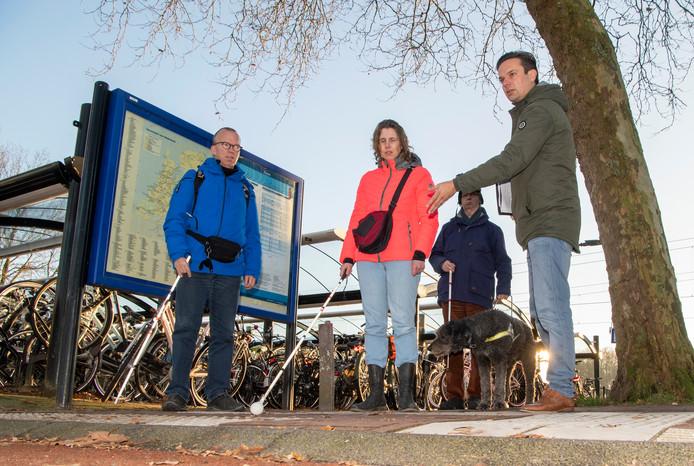 Marc Oortman (links), Anita Beenen en Sido van Eck (met hond Jackson) in gesprek met beleidsmedewerker Frans Mosterman van de gemeente Dalfsen. Ze zijn tevreden over de maatregelen die op het station zijn getroffen voor visueel beperkten.