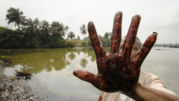 Man laat vervuilde bodem zien in Nigeria Beeld ANP