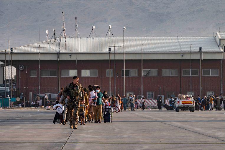 Een Amerikaanse soldaat begeleidt Afghanen naar evacuatievliegtuig op de luchthaven in Kaboel. Beeld AP