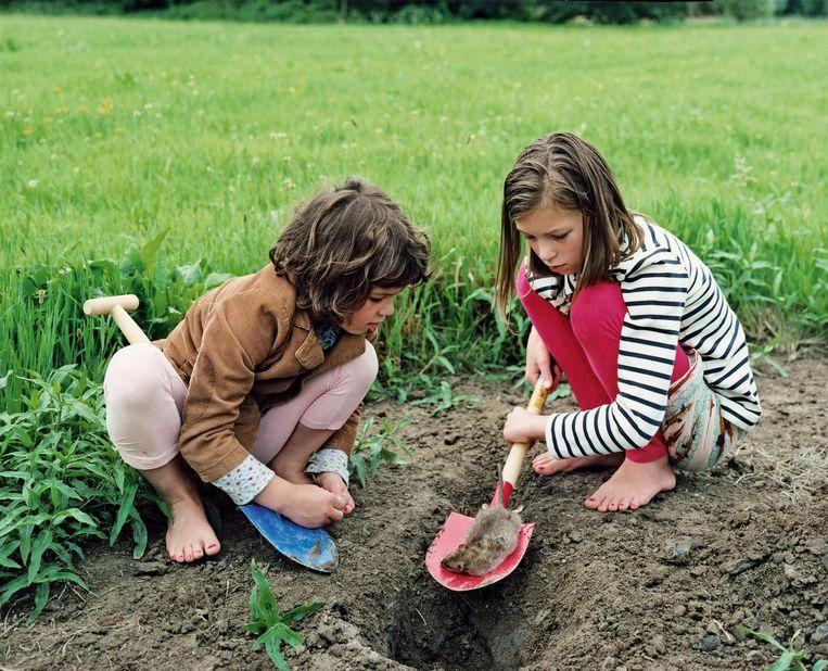 Twee meisjes zijn geconcentreerd bezig met een dode rat te begraven. Beeld null